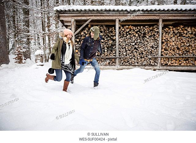Happy couple running in front of wood pile outdoors in winter