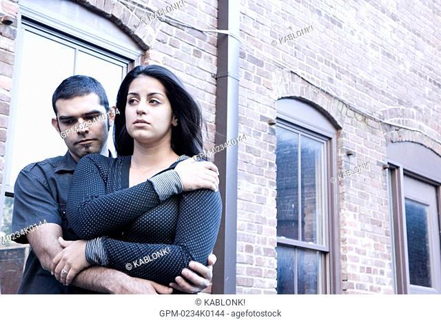 Young Hispanic couple embracing near brick building