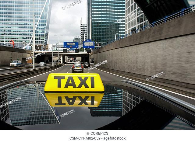 City taxi driving over a motorway in a commercial district