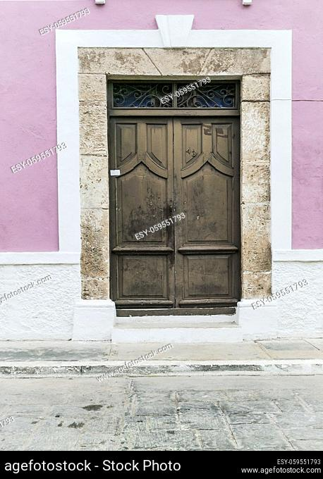 Close up of large brown wooden door with stone door trim on a pink and white stucco Spanish colonial house, Campeche, Mexico