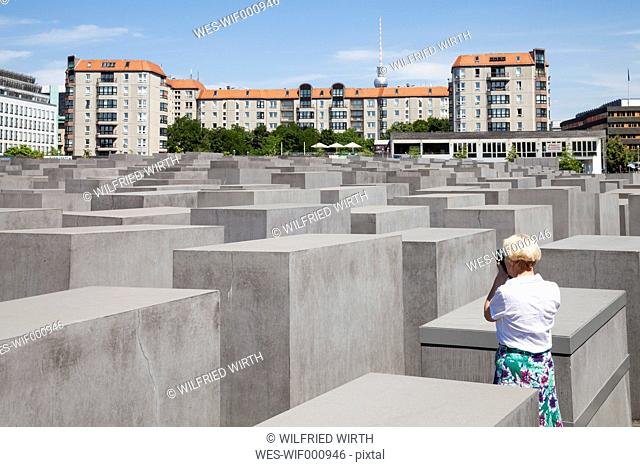 Germany, Berlin, Holocaust Memorial, Mature woman photographing steles