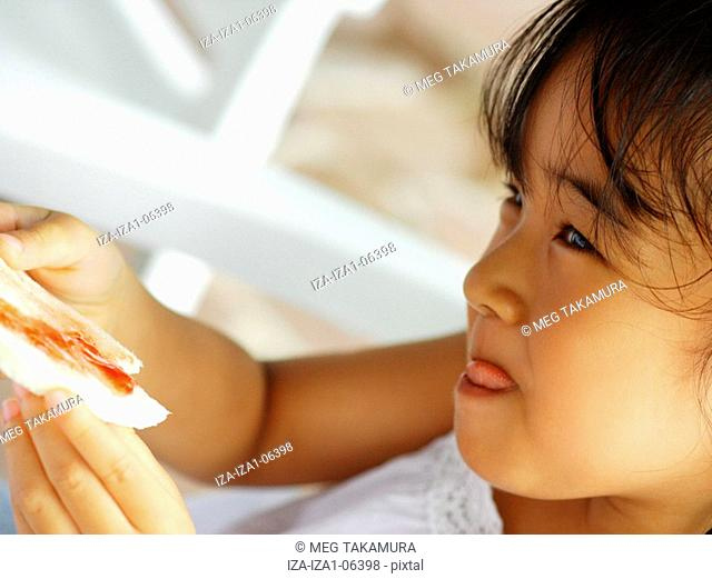 Close-up of a girl holding a slice of bread