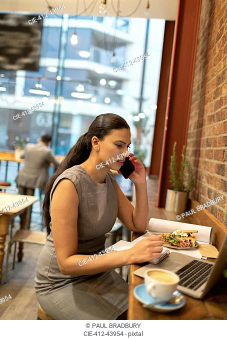 Businesswoman talking on smart phone, working at laptop in cafe