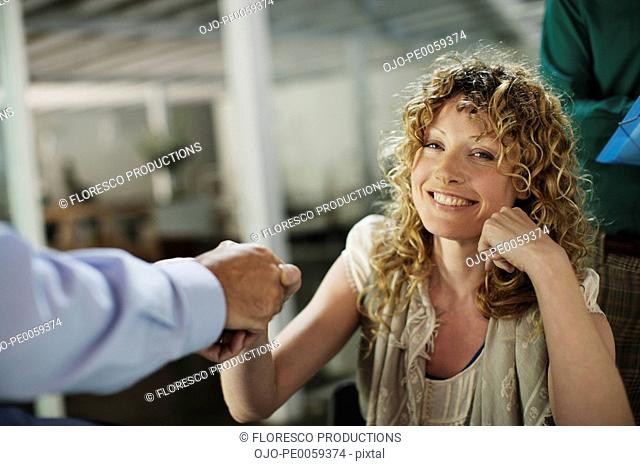 Woman shaking businessman's hand with man in background