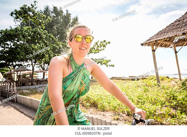 Woman cycling near coast, Gili Trawangan, Lombok, Indonesia