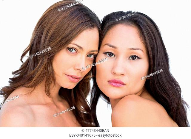 Beautiful nude models posing head against head on white background