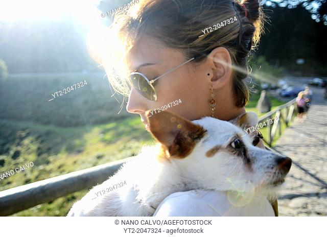 Attractive young woman poses with her small white dog