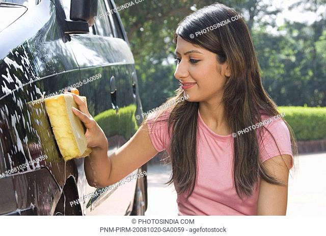 Woman washing a car and smiling, New Delhi, India
