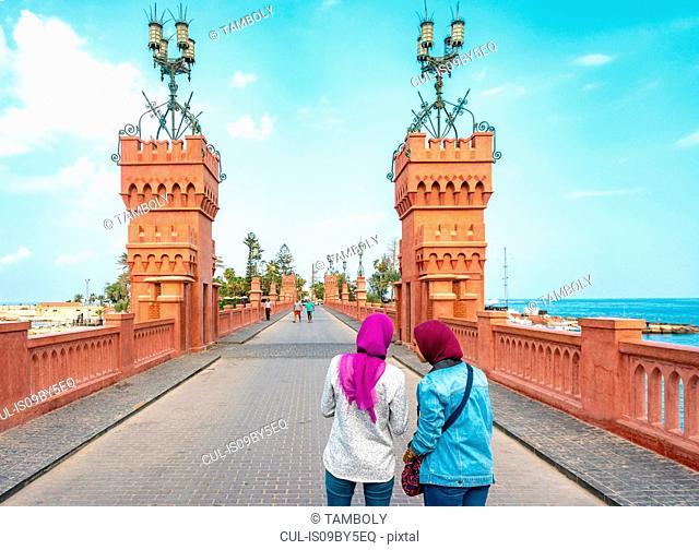 Two female tourists taking photograph on Montaza palace bridge, Alexandria, Egypt