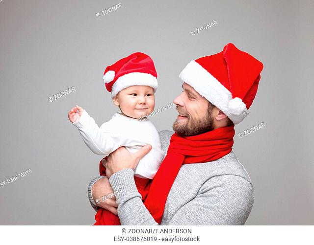 Father with his baby boy wearing Santa hats celebrating Christmas