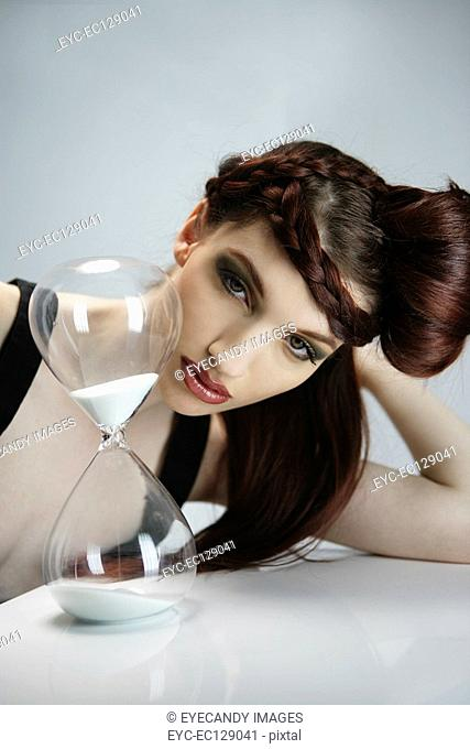 Portrait of stylish woman with retro hairstyle watching sand in hourglass tick away, studio shot