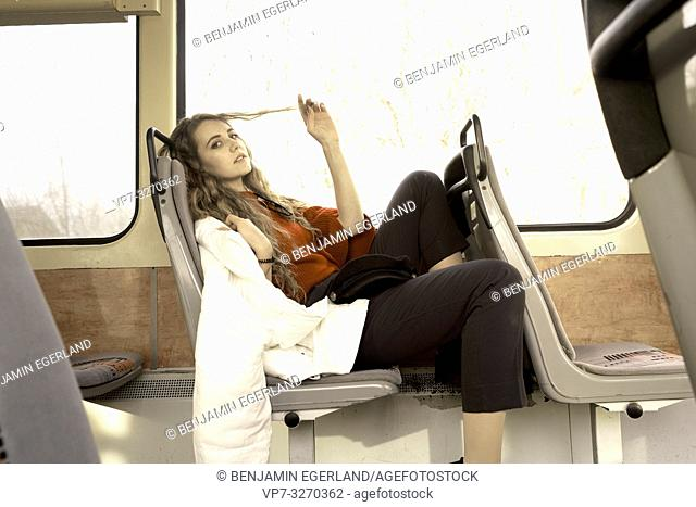 young woman sitting in public transport, playing with hairs, in city Cottbus, Brandenburg, Germany