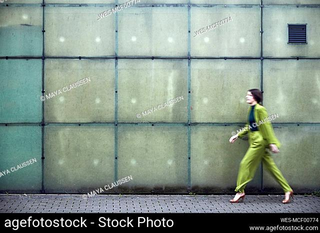 Businesswoman wearing green suit passing a wall
