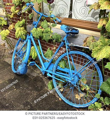 Blue painted bicycle standing under a window