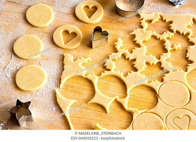 Preparation of traditional Linzer Christmas cookies - cutting out star and heart shapes from rolled out dough