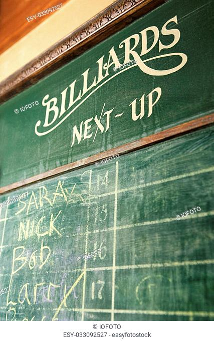 Chalkboard queue for people waiting to play billiards in nightclub