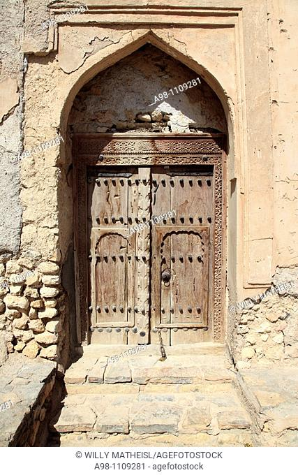 old wooden door in front of the facade of Fort Quriat in the village Quriat, Sultanate of Oman, Asia