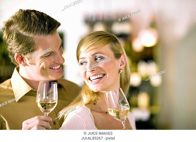 Couple drinking white wine and smiling at each other indoors