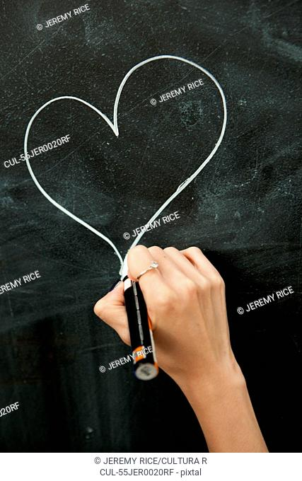 Young woman drawing heart on blackboard