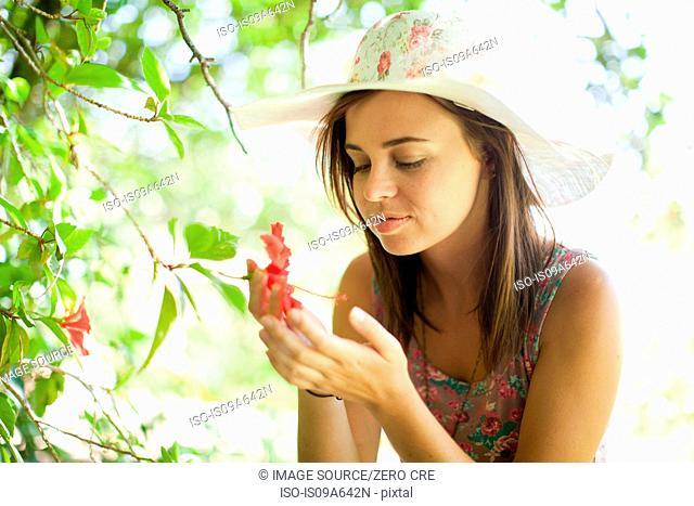 Woman admiring flower in park