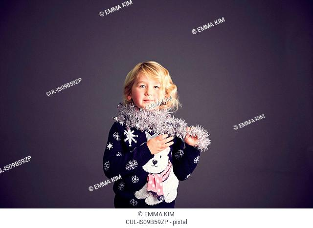 Portrait of young girl wearing Christmas jumper and tinsel around neck