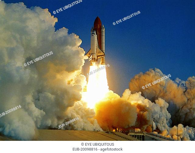 NASA Space Shuttle lifting off amidst thick white clouds of smoke and flames from rocket boosters