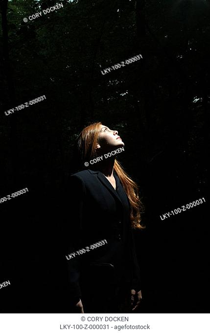 Woman's face illuminated by sunlight in forest