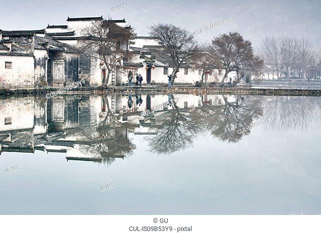 Mirror image of bare trees and traditional houses by lake, Hongcun Village, Anhui Province, China