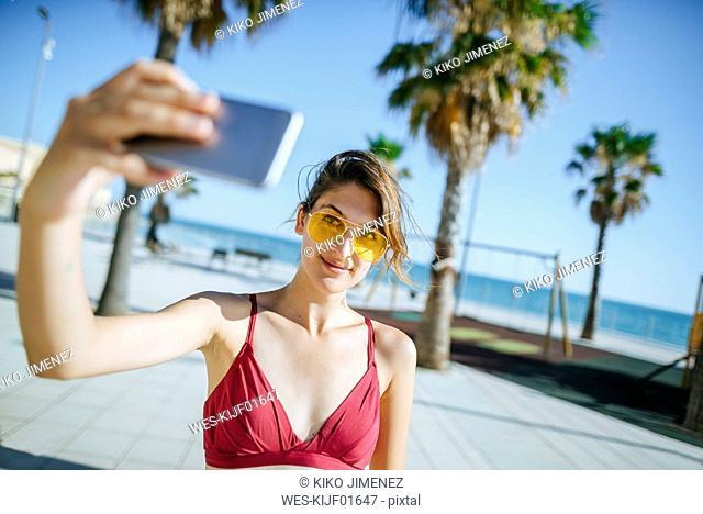Young woman wearing yellow sunglasses taking a selfie on boardwalk
