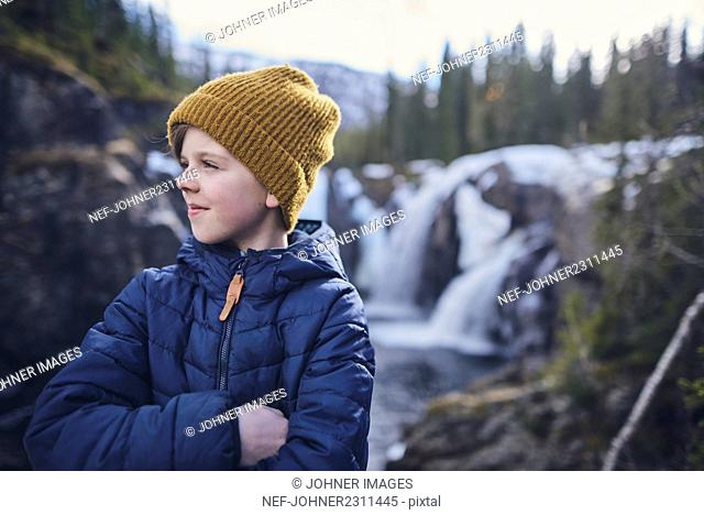 Portrait of boy with waterfall in background