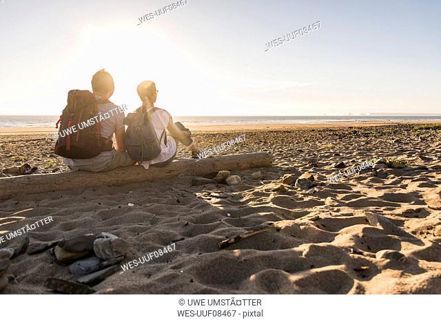 France, Bretagne, Finistere, Crozon peninsula, couple during beach walk, sitting on beach, enjoying sunset