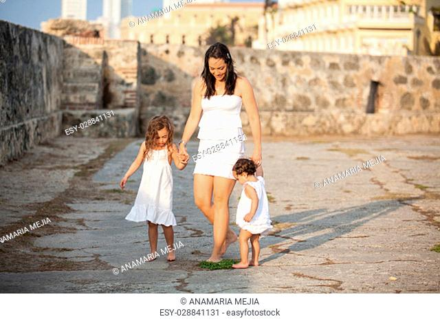 Mother and her daughters dressed in white walking along Cartagena's Wall