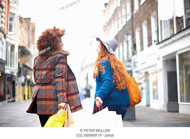 Two young women, walking along street, holding shopping bags, rear view