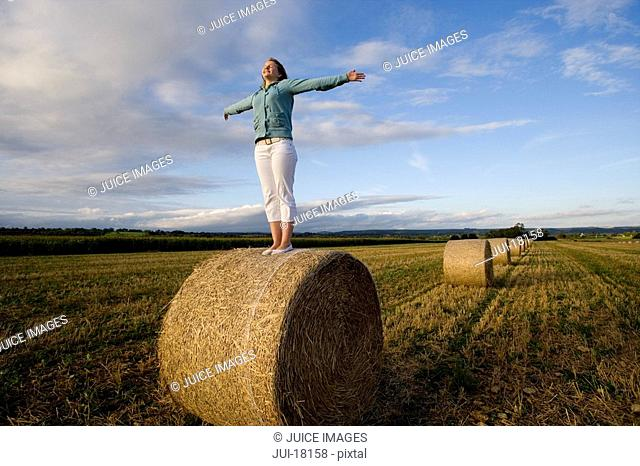 Teenage girl 16-18 standing on bale of hay in field with arms outstretched