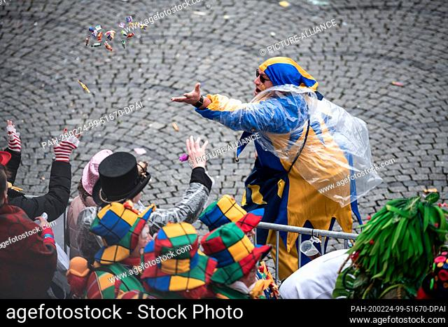 24 February 2020, North Rhine-Westphalia, Duesseldorf: A carnivalist throws camels into the audience. With the Rosenmontag parades the Rhenish street carnival...