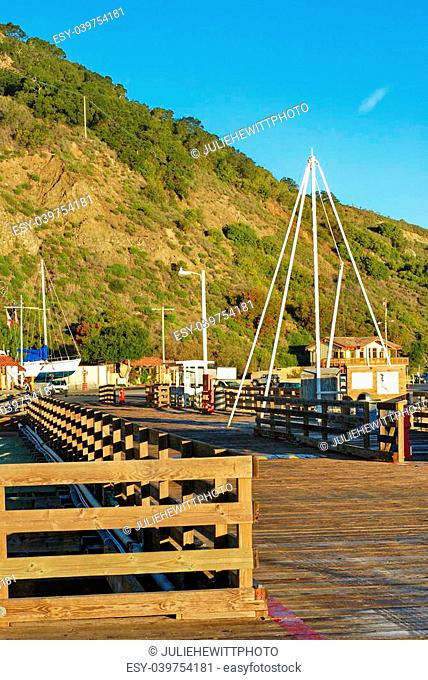 This long pier located on Avila Beach, CA is photographed on a cool bright, early morning with a brilliant blue sky. The frost still lingers on the gnarled wood...