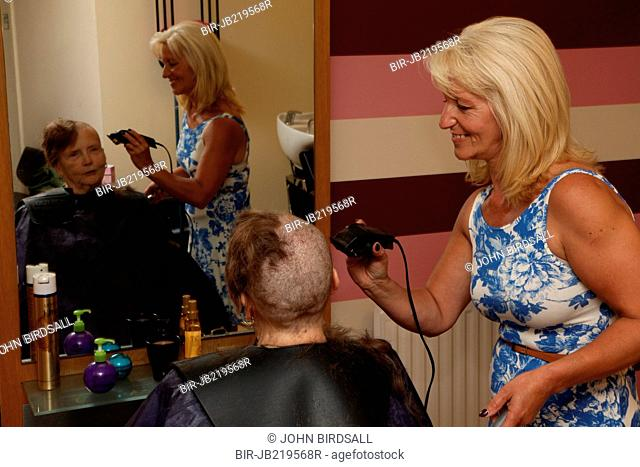 Woman having her head shaved as a fundraiser for the charity Mysight