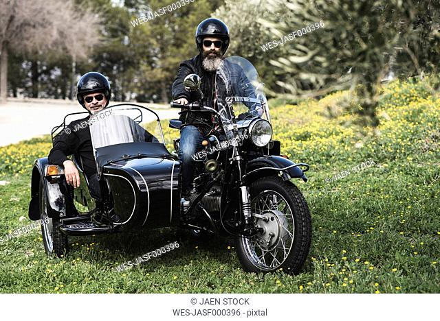 Portrait of two bikers standing with their sidecar motorcycle on a meadow