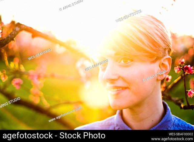 Close-up of thoughtful woman with sunlight in background at park during sunset