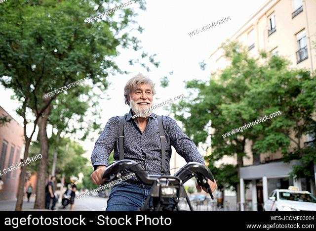 Smiling mature man looking away while riding electric bicycle in city