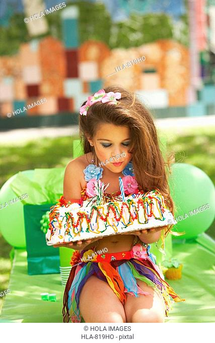 Close-up of a girl blowing out candles on a birthday cake