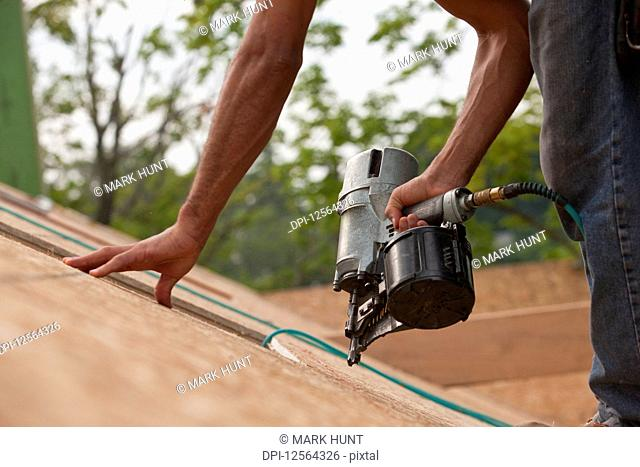 Hispanic carpenter using a nail gun on the roof panel of a house under construction
