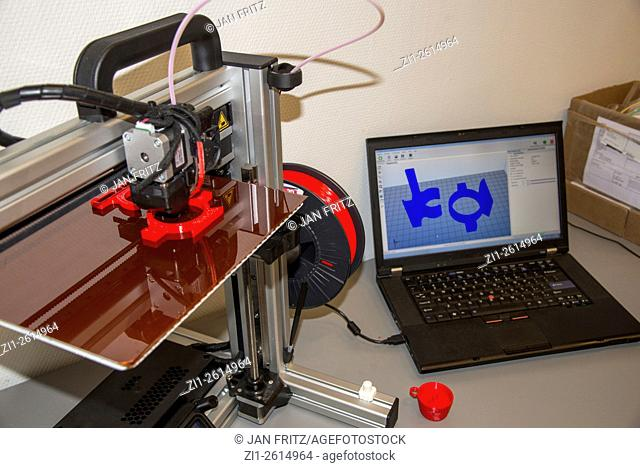 3 dimensional printer at work with laptop with graphic model