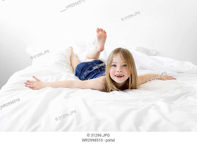 A six year old girl lying on a bed with her arms out, looking at the camera