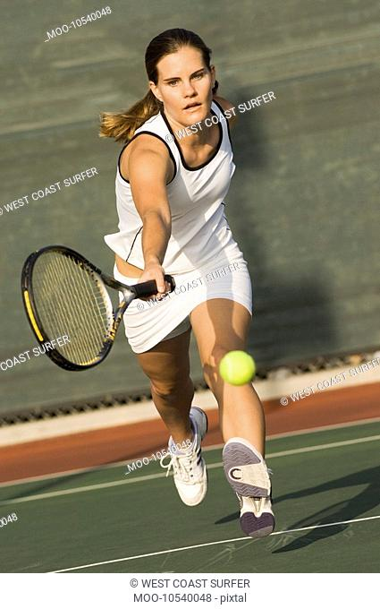 Tennis Player Reaching to hit tennis ball on tennis court