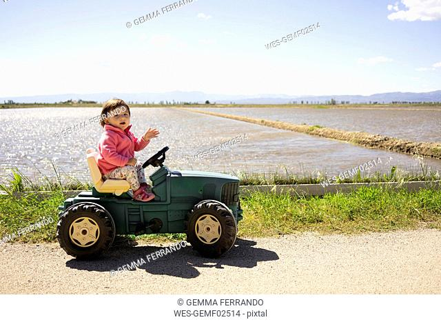 Baby girl driving a toy tractor next to the rice fields