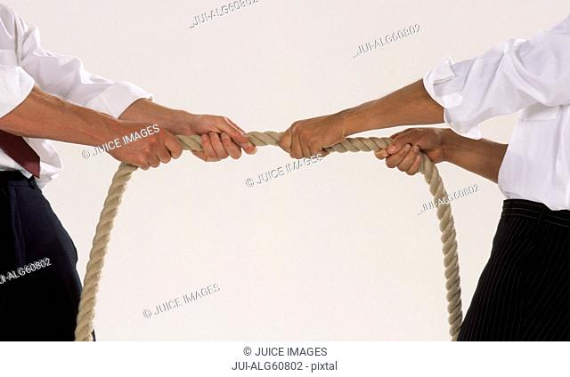Detail of two businessmen in shirtsleeves engaged in tug-of-war