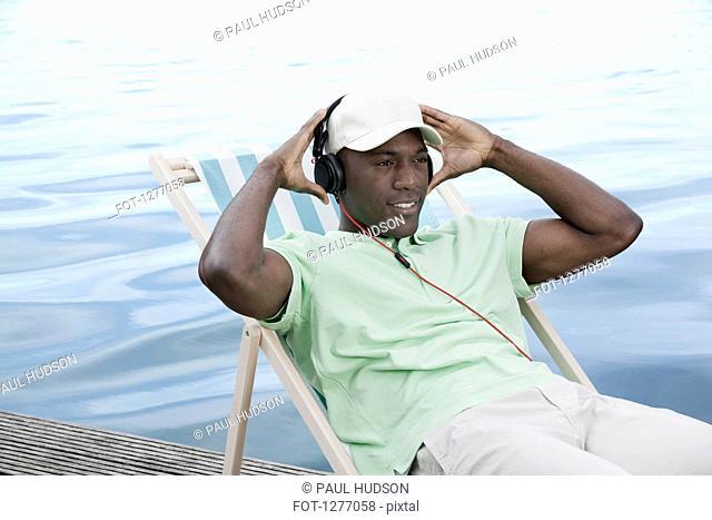Man relaxing on deck chair by lake wearing headphones