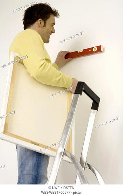 Young man on ladder holding spirit level on wall, low angle view