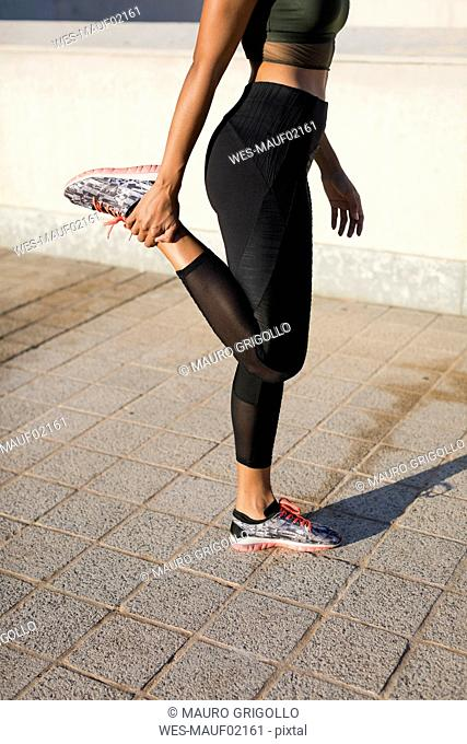 Close-up of young woman doing stretching exercise in the city
